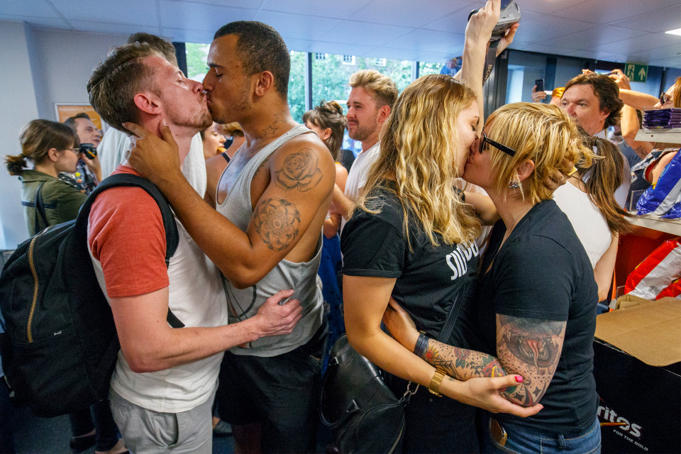 © Licensed to London News Pictures. 13/08/2016. London, UK. Gay couples stage a big kiss in protest at Sainsbury's in Hackney, east London on Saturday, 13 August 2016. Protest is as a reaction to a security guard in Sainsbury's on Hackney Road allegedly told a shopper that holding hands with his boyfriend was 'inappropriate' on Monday. Photo credit: Tolga Akmen/LNP